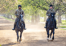 Licensed to London News Pictures. 20/04/2021. London, UK. Cavalry with swords drawn, exercise their horses in the warm sunshine in Hyde Park London this morning a week after the easing of Covid-19 restrictions as a mini heatwave hit the UK this week with temperatures reaching over 18c in London and the South East. Photo credit: Alex Lentati/LNP