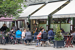 © Licensed to London News Pictures. 04/07/2020. London, UK. Restaurant goers enjoy a sit down coffee and meal at the Olympic Studio cinema and restaurant in Barnes Village, South West London as members of the public flock to pubs, restaurants, hairdressers, hotels and campsites for the first time in over 100 days as the unlocking of the coronavirus pandemic restrictions continues.  Photo credit: Alex Lentati/LNP
