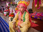 "04 APRIL 2015 - CHIANG MAI, CHIANG MAI, THAILAND:  A Tai boy at Wat Pa Pao during the Poi Sang Long Festival. Friends and family will visit him and pray with him before the ordination ceremony. The Poi Sang Long Festival (also called Poy Sang Long) is an ordination ceremony for Tai (also and commonly called Shan, though they prefer Tai) boys in the Shan State of Myanmar (Burma) and in Shan communities in western Thailand. Most Tai boys go into the monastery as novice monks at some point between the ages of seven and fourteen. This year seven boys were ordained at the Poi Sang Long ceremony at Wat Pa Pao in Chiang Mai. Poy Song Long is Tai (Shan) for ""Festival of the Jewel (or Crystal) Sons.     PHOTO BY JACK KURTZ"