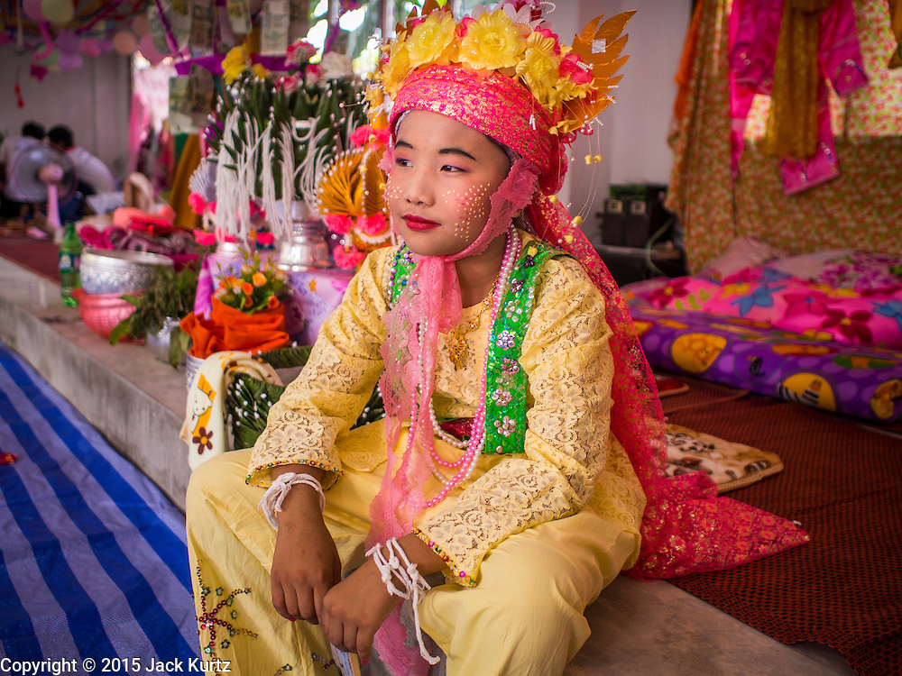 """04 APRIL 2015 - CHIANG MAI, CHIANG MAI, THAILAND:  A Tai boy at Wat Pa Pao during the Poi Sang Long Festival. Friends and family will visit him and pray with him before the ordination ceremony. The Poi Sang Long Festival (also called Poy Sang Long) is an ordination ceremony for Tai (also and commonly called Shan, though they prefer Tai) boys in the Shan State of Myanmar (Burma) and in Shan communities in western Thailand. Most Tai boys go into the monastery as novice monks at some point between the ages of seven and fourteen. This year seven boys were ordained at the Poi Sang Long ceremony at Wat Pa Pao in Chiang Mai. Poy Song Long is Tai (Shan) for """"Festival of the Jewel (or Crystal) Sons.     PHOTO BY JACK KURTZ"""
