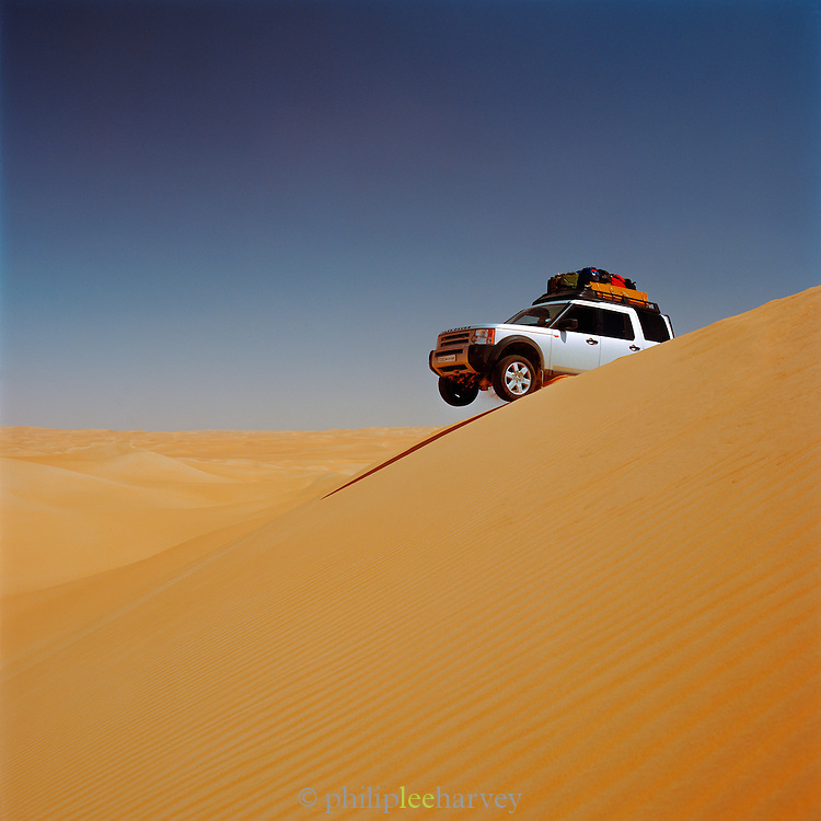 4x4 off-road vehicle driving over the crest of a sand dune, Sahara desert, Libya
