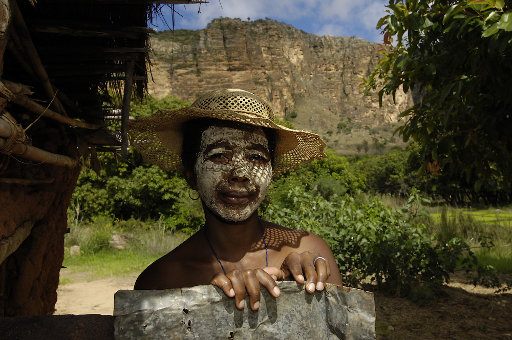 Local woman with sandalwood face mask - used as sun protection and a beautification. Sandstone Massif. Isalo National Park<br />MADAGASCAR<br />Isalo was declared a National Park in 1962. This is a sacred area to the Bara tribe who have used caves in the canyon walls as burial sites for centuries. The park was created to protect the rare endemic plants in the region as well as the 7 species of lemurs found there.