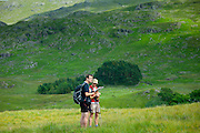 Couple walking through Hard Knott Pass check their map reading in the Lake District National Park, Cumbria, UK