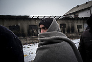 A migrants protects himself from the cold and the snow while waiting in line for a food distribution. Belgrade, Serbia. January 17th, 2017. Federico Scoppa