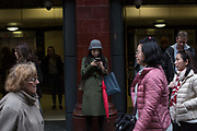 A girl uses her mobile phone outside Covent Garden Underground Station on 19th December 2016 in London, United Kingdom. From the series Our Small World, an observation of our mobile phone obsessions