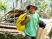 """A Laoseng ethnic minority man carries a piece of metal roofing material through the old village to his village of Ban Watai has been temporarily relocated away from the Nam Ou river, during the construction of the Nam Ou Cascade Hydropower Project Dam 6, Phongsaly province, Lao PDR. The Nam Ou river connects small riverside villages and provides the rural population with food for fishing. It is a place where children play and families bathe, where men fish and women wash their clothes. But this river and others like it, that are the lifeline of rural communities and local economies are being blocked, diverted and decimated by dams. The Lao government hopes to transform the country into """"the battery of Southeast Asia"""" by exporting the power to Thailand and Vietnam."""
