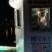 Hasegawa-san preparing his fishing boat early in the morning. Hasegawa-san specializes in deep-sea fishing.