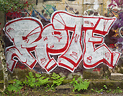 Street art painting in old mill building in Vernonia, Oregon depicting red and white abstract word