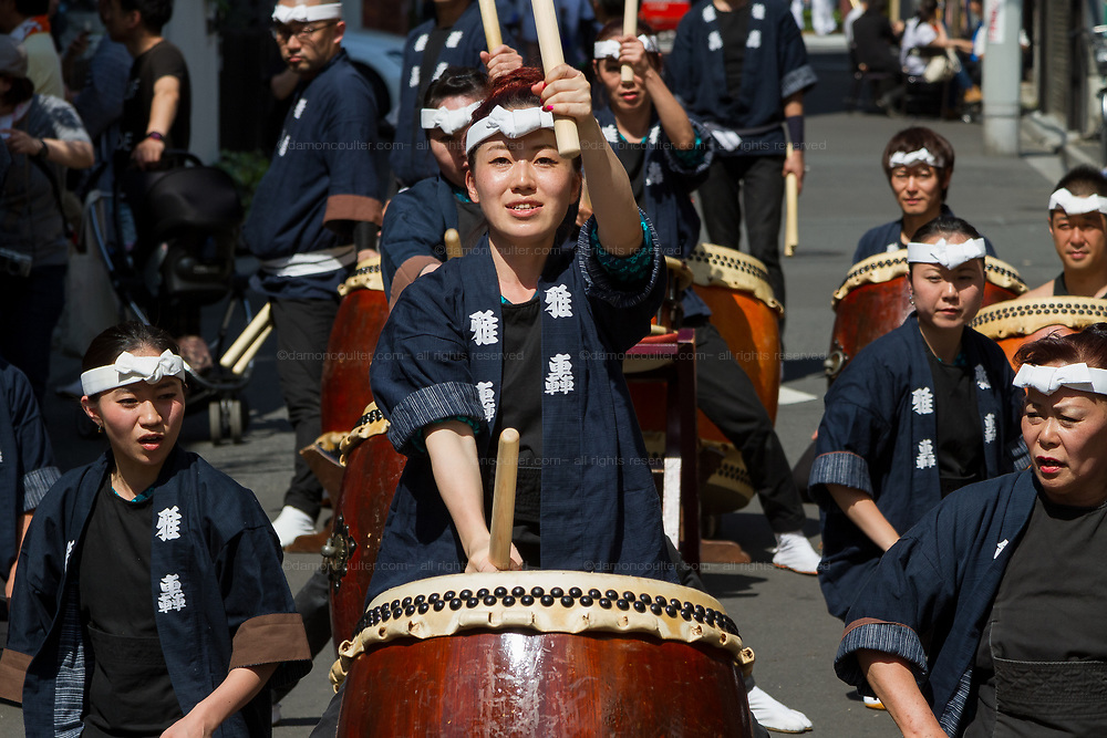 Women play large taiko drums during the Sanja matsuri, Asakusa, Tokyo, Japan. Sunday May 21st 2017. The Sanja matsuri (Three shrines festival) is one of the biggest Shinto festivals in Japan. It takes place for 3 days around the third weekend of May and features over 100 large and small mikoshi, or portable shrines, which are paraded around the streets of the historic Asakusa district in Tokyo. to bring blessings and good luck on the inhabitants. The events attracts up to 2 million visitors each year.