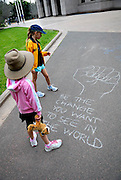 Two children (6 years old, 10 years old) reading graffiti chalked onto footpath. Hyde Park, Sydney, Australia