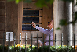 © Licensed to London News Pictures. 11/09/2021. London, UK. A man reaches out to a plaque containing names of the British victims at the  September 11 Memorial Garden in Grosvenor Square, London on the 20th anniversary of the 9/11 terrorist attack. The attacks, which killed a total of 2,977 people - 67 of them British - saw passenger jets seized by suicide attackers, flown into the Twin Towers of the World Trade Center in New York and the The Pentagon building in Washington. Photo credit: Peter Macdiarmid/LNP
