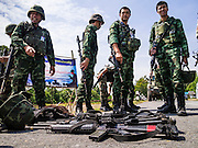 11 JULY 2013 - RAMAN, YALA, THAILAND:  Thai soldiers look at the weapons and equipment of their colleagues injured in an IED attack Thursday morning. A billboard urging peace during the holy month of Ramadan is behind the soldiers. Eight soldiers were injured when the IED exploded under a Thai Army truck carrying soldiers back to their camp after they finished a teacher protection mision. The army routinely dispatches soldiers to protect teachers and Buddhist monks, who have been targeted by Muslim insurgents as representatives of the Bangkok government. More than 5,000 people have been killed and over 9,000 hurt in more than 11,000 incidents in Thailand's three southernmost provinces and four districts of Songkhla since the insurgent violence erupted in January 2004, according to Deep South Watch, an independent research organization that monitors violence in Thailand's deep south region that borders Malaysia.   PHOTO BY JACK KURTZ