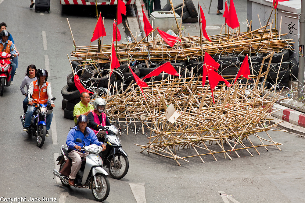 Apr. 30 - BANGKOK, THAILAND: Motorcycle taxis take passengers past a Red Shirt barricade in the Siam section of Bangkok Friday.  The Red Shirts moved one of their barricades in the Sala Daeng Intersection in Bangkok Friday In one of the first positive moves to take place since the Red Shirts occupied central Bangkok in early April. The barricade was moved far enough back to open one lane of traffic on  Ratchadamri Street to allow ambulance access to King Chulalongkorn Memorial Hospital, a large hospital at the intersection. Many of the patients in the hospital have been moved to other hospitals because a group of Red Shirts entered the hospital Thursday looking for Thai security personnel, who were not in the hospital. The stand off between the Red Shirts and the government enters its third month in May. The Red Shirts continue to call for Thai Prime Minister Abhisit Vejjajiva to step down and dissolve parliament and demand the return of ousted Prime Minister Thaksin Shinawatra.   PHOTO BY JACK KURTZ