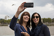 Women take a selfie on a mobile phone. Totally Thames takes place over the whole month in September, combining arts, cultural and river events presented by Thames Festival Trust throughout the 42-mile stretch of the River Thames in London, UK.