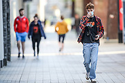 People some of them wearing face protective covering masks walk across the city centre in Belfast, Northern Ireland on Monday, April 26, 2021. (Photo/ Vudi Xhymshiti)