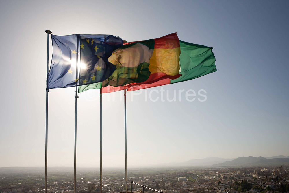 The Spanish, Andalucian and EU flags fly high over city of Granada on top of Alhambra's Torre de la Vela (Watchtower). In a strong mountain breeze the fabric whips on their flagpoles as the sun is placed behind, allowing the backlighting to give this landscape a sense of nationalism and patriotism. The stars of the EU member countries and Spain's national flag rise above the distant homes in this Andalucian city.