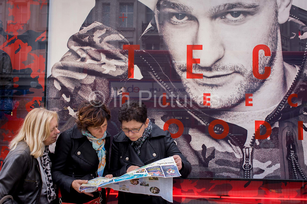 Women tourists pause to look at a map of central London (Londres) beneath a large male model's face advertising Nike's Tech Fleeces. With the model's large face gazing steadily outwards from the shop's window, we see the eiptome of male beauty - a handsome and rugged male to seduce women shoppers into the Nike store. Underneath we see the three women consulting their map of central London - seeking directions to their next location.