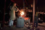 Klokkengieter Simon Laudy (links) roert in de bak met brons van 1100 graden. Op de Domplein in Utrecht wordt een klok gegoten dat door de Utrechtse Klokkenluidersgilde wordt geschonken aan het  Academiegebouw van de Universiteit Utrecht ter gelegenheid van hun 375 jarig bestaan in 2011. Het is voor het eerst sinds eeuwen dat weer een klok in het openbaar wordt gegoten. De klok gaat Anna Maria (genoemd naar de eerste vrouwelijke student aan de universiteit, Anna Maria van Schurman) heten en is gemaakt van brons.<br /> <br /> Bell-founder Simon Laudy (left) is pouring the hot bronze during the casting of a new bell. For the first time in centuries a bell is being casted publicly at the Domplein in Utrecht. The 100 kg bronze bell is a present of the Utrecht Bell-ringing Guild to the University Utrecht which is celibrating its 375 year's anniversary in 2011. The bell is named Anna Maria after the first female student of the university.