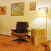 A Eames chair with a black back support pillow next to a large yellow-red marble triangular shaped block with a white intercom phone on top and a brass floor lamp to the right of the block.There are four Impressionist posters on stripped wallpaper behind and above the chair, and a very large Oriental style carpet covering almost all of the floor.