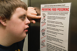 Teenaged boy with Downs Syndrome reading about food hygiene from a poster at special school,