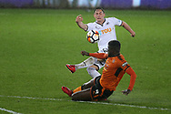 Connor Roberts of Swansea city has a shot at goal as Alfred N'Diaye of Wolverhampton Wanderers slides in to tackle.  The Emirates FA Cup, 3rd round replay match, Swansea city v Wolverhampton Wanderers at the Liberty Stadium in Swansea, South Wales on Wednesday 17th January 2018.<br /> pic by  Andrew Orchard, Andrew Orchard sports photography.