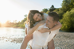Mature man giving piggyback ride to his wife at lakeside, Bavaria, Germany