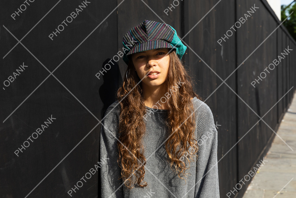 Emotionless girl with colorful hat and long brown hair. Urban context and black background.