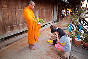 "10 JULY 2011 - AMPHAWA, SAMUT SONGKRAM, THAILAND:  A Buddhist monk prays for some women who just presented him with alms during his morning alms rounds in Amphawa, Thailand. The Thai countryside south of Bangkok is crisscrossed with canals, some large enough to accommodate small commercial boats and small barges, some barely large enough for a small canoe. People who live near the canals use them for everything from domestic water to transportation and fishing. Some, like the canals in Amphawa and nearby Damnoensaduak (also spelled Damnoen Saduak) are also relatively famous for their ""floating markets"" where vendors set up their canoes and boats as floating shops.       PHOTO BY JACK KURTZ"