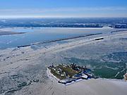 Nederland, Noord-Holland, Gemeente Waterland, 13-02-2021; winterlandschap, Vuurtoreneiland met Vuurtoren Hoek van 't IJ. In het Buiten IJ is de vaargeul open gehouden door ijsbrekers, binnenvaartschip onderweg naar Oranjesluizen. IJburg in de achtergrond. <br /> Winter landscape, Lighthouse Island. In the Buiten IJ, the navigation channel has been kept open by icebreakers, an inland vessel on its way to Oranjesluizen. IJburg in the background.<br /> <br /> luchtfoto (toeslag op standaard tarieven);<br /> aerial photo (additional fee required)<br /> copyright © 2021 foto/photo Siebe Swart