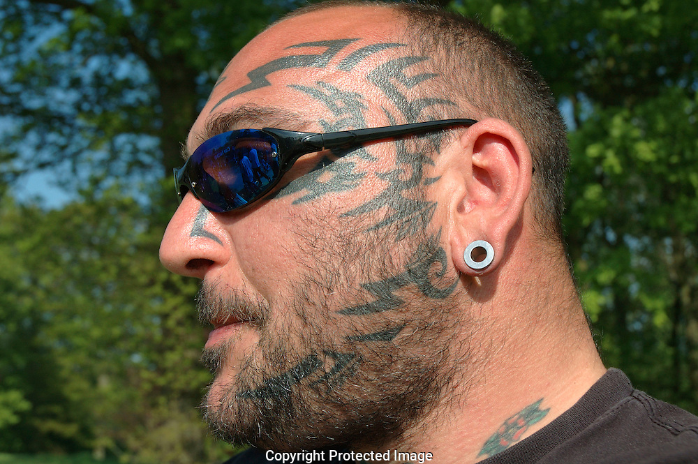Portrait of man with dark glasses and tattoos on face and arms and piercings.