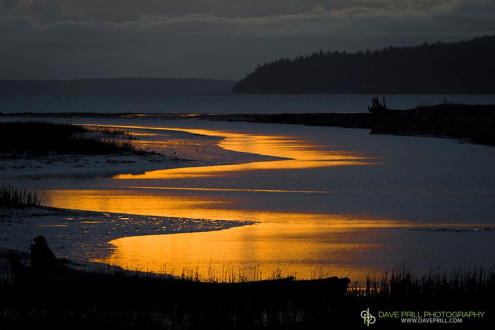 Sunset at Skagit Delta on Fir Island. reflection of sun shining through cloud formation.