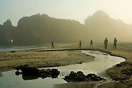 People walking next to stream flowing through sand below coastal rocks and fog at sunset, Pfeiffer Beach, Big Sur Coast, Monterey County, California