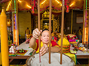 12 OCTOBER 2015 - BANGKOK, THAILAND: A man makes merit at Wat Mangkon Kamlawat, a large Chinese temple in Bangkok, on the first day of the Vegetarian Festival in Bangkok's Chinatown. The Vegetarian Festival is celebrated throughout Thailand. It is the Thai version of the The Nine Emperor Gods Festival, a nine-day Taoist celebration beginning on the eve of 9th lunar month of the Chinese calendar. During a period of nine days, those who are participating in the festival dress all in white and abstain from eating meat, poultry, seafood, and dairy products. Vendors and proprietors of restaurants indicate that vegetarian food is for sale by putting a yellow flag out with Thai characters for meatless written on it in red.      PHOTO BY JACK KURTZ
