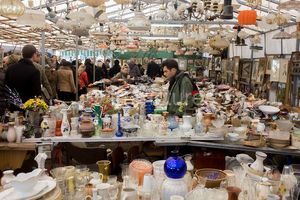 Glassware, crockery, bric-a-brac and old possessions being sold at a giant market in Mauerpark - an open space on the site of the old Berlin wall, the former border between Communist East and West Berlin during the Cold War. The flea market is visited by tourists and local Berliners and tourists alike, taking place every Sunday on Bernauer Strasse where the wall turned sharp left and cut through where stallholders now offer their wares.