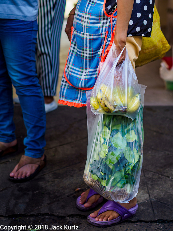 20 JUNE 2018 - BANGKOK, THAILAND: A shopper with her purchases in plastic bags at Makkasan Market, a small local market in central Bangkok. Officials in Thailand are wrestling with Thais use of plastic bags. The issue became a public one in early June when a whale in Thai waters died after ingesting 18 pounds of plastic. In a recent report, Ocean Conservancy claimed that Thailand, China, Indonesia, the Philippines, and Vietnam were responsible for as much as 60 percent of the plastic waste in the world's oceans.     PHOTO BY JACK KURTZ