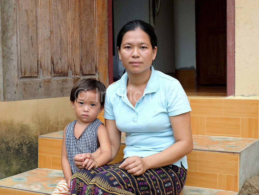 Phatthida Chanmany and her daughter outside their home in Namai Village, Feung District, Vientiane Province, Laos. 210-year-old  Namai village, home to 878 people, has changed significantly over the past 15 years, with the arrival of a paved road, electricity and clean drinking water. But alongside this welcome progress climate change has brought unprecedented and unpredictable new weather patterns, disrupting harvests and lifestyles in this farming-dependent community.