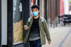 © Licensed to London News Pictures. 17/03/2020. Leeds UK. A man wears a face mask as the Streets in Leeds city centre are almost empty after yesterdays announcement that people should work from home & everyone should avoid pubs, clubs & restaurants. Photo credit: Andrew McCaren/LNP