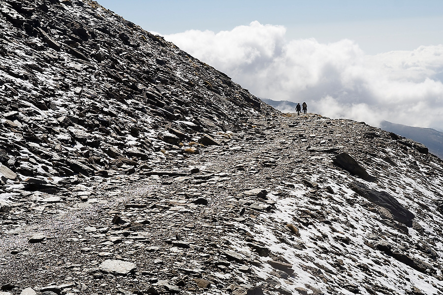 Two people hike the trail to Mulhacen which begins at Capileira, a village in the Alpujarra mountains, Sierra Nevada National Park, Andalusia, Spain.