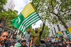 © Licensed to London News Pictures. 15/08/2019. LONDON, UK.  A flag waver joins thousands of protesters, many waving Pakistani and Kashmiri flags, outside the Indian High Commission in Aldwych, on what they are calling Black Day, to stand in solidarity with the people of Kashmir.  Indian Prime Minister Narendra Modi delivered an Independence Day speech highlighting his decision to remove the special rights of Kashmir as an autonomous region.  Photo credit: Stephen Chung/LNP