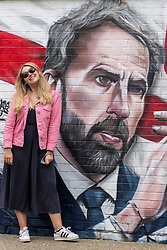 © Licensed to London News Pictures. 14/07/2021. London, UK. A woman poses next to the mural of the England football team including manager GARETH SOUTHGATE and footballers HARY KANE and RAHEEM STIRLING (not seen) which has been unveiled near London. Bridge. The mural created by Marc Silver of MurWalls, is a celebration of a team that has united the nation. Photo credit: Ray Tang/LNP