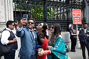 Pro Brexit protesters part of the same scene as people who have been attending a private function inside the Houses of Parliament mill around taking selfies, meanwhile the Tory leadership race continues on 17th June 2019 in London, England, United Kingdom.