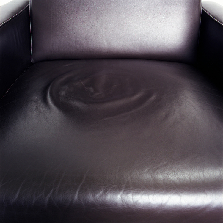 Looking down at the seat of a black leather chair, with the circular impression from someone's bottom creating a ripple effect.