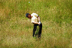 Nick Price takes the ball out of the rough on the sixth hole