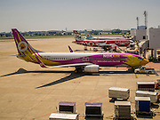 02 APRIL 2015 - BANGKOK, THAILAND:   NOK Airlines and Air Asia aircraft at their gates at Don Mueang Airport in Bangkok. The International Civil Aviation Organization (ICAO), a United Nations agency, issued a report critical of record keeping and maintenance reports for Thailand's civil aviation industry, including most Thai air carriers. The ICAO report allegedly showed that the Thai Department of Civial Aviation (DCA) was able to meet only 21 out of 100 ICAO requisites. Several Asian countries, including South Korea, Japan and China have imposed limits of Thai registered aircraft since the release of the ICAO report and the European Union has begun to review the safety records of Thai Airways International (THAI) aircraft that fly to Europe.    PHOTO BY JACK KURTZ