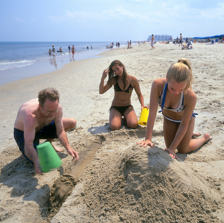 Stephen Haeckel, left, collaborates with daughter Reed and her friend Spunky to build a sand castle at the Henlopen Acres Beach Club in Rehoboth Beach, Del., Sunday, Aug. 9, 2009. (Photo by D. Ross Cameron)