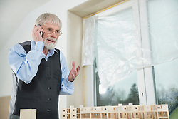 Architect telephoning at construction site of new building