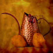 Still life of copper watering can, pears and grapes