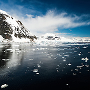 Scenic landscape on the Antarctic Peninsula, with small blocks of ice floating on the water in the foreground and mountains in the background.