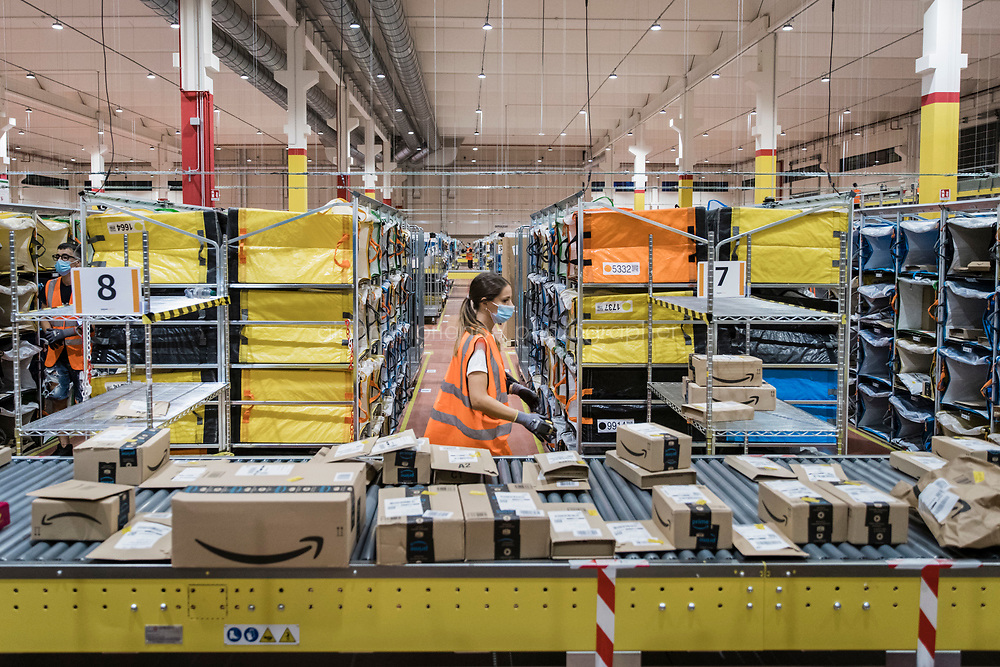 ARZANO, ITALY - 18 SEPTEMBER 2020: A stower processes Amazon packages at the Amazon delivery station in Arzano, just outside Naples, Italy, on September 18th 2020.<br /> <br /> Opened in 2019, the Amazon delivery station in Arzano was the first to open in Southern Italy. Here, an average of 30,000 to 50,000 Amazon packages are processed and delivered in the region.<br /> <br />    plans to open two new fulfillment centers and seven delivery stations. Roughly 1,600 more people will be hired by the end of the year, pushing its full-time work force in Italy to 8,500 from less than 200 in 2011. <br /> <br /> Amazon has been one of the biggest winners in the pandemic as people in its most established markets — the United States, Germany and Britain — have turned to it to buy everything from toilet paper to board games. What has been less noticed is that people in countries that had traditionally resisted the e-commerce giant are now also falling into Amazon's grasp .<br /> The shift has been particularly pronounced in Italy, which was one of the first countries hard hit by the virus. Italians have traditionally preferred to shop at local stores and pay cash. But after the government imposed Europe's first nationwide virus lockdown, Italians began shopping online in record numbers. <br /> 75 percent of Italians shopped online during the lockdown. In 2020, total online sales are estimated to grow 26 percent to a record 22.7 billion euros, according to researchers from Polytechnic University of Milan.