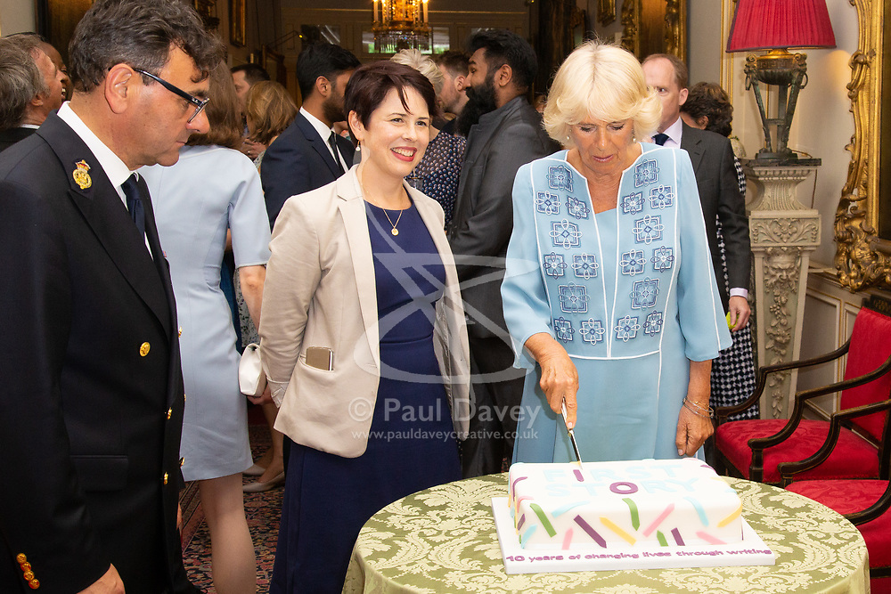 Her Royal Highness Camilla the Duchess of Cornwall hosts a reception at Clarence House to mark the tenth anniversary of First story, an initiative to encourage writing in especially among those from deprived backgrounds in schools across the country PICTURED: Camilla cuts the cake as Monica Parle, Executive Director of First Story looks on. London, July 10 2018.